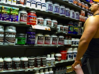 Bodybuilder looking at Pre Workout Supplements on a Store Shelf