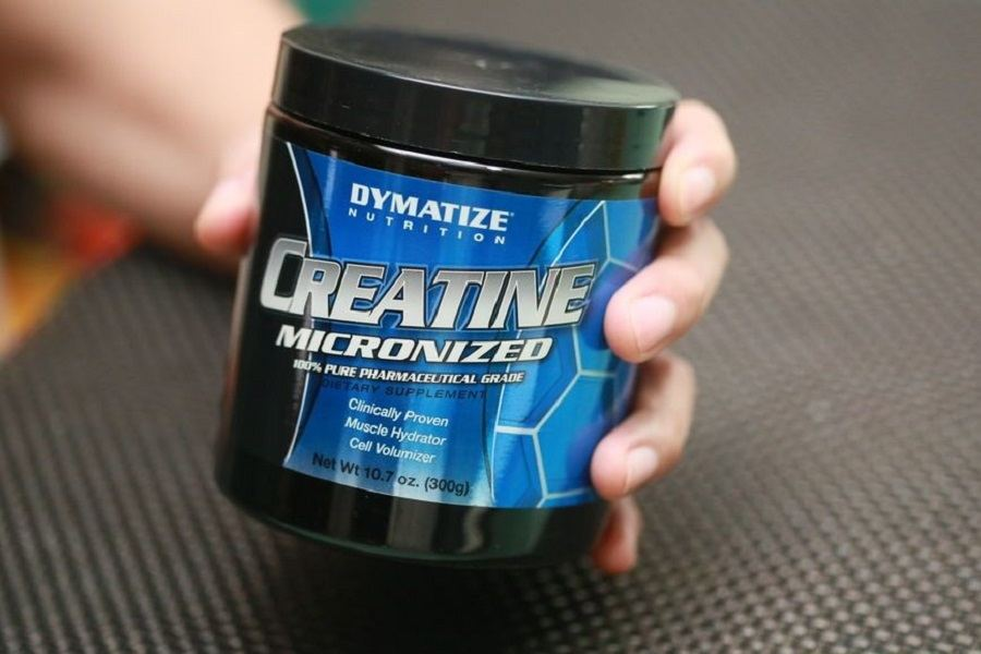 Hand Holding Dymatize Nutritions Creatine Powder